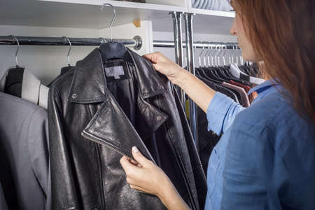 Portrait of a red-haired girl in a women's clothing and business suit shop chooses a leather jacket. Background for shopping, clearance sale, black friday. Discounts on leather goods at a women's store