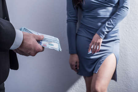 close-up, out of focus, a man in a business suit holding dollar bills in his hand, gives money to a prostitute standing against the wall, in a dress, out of focus. Studio shooting on a gray background. the concept of prostitution. Girls of easy virtue. A client gives money to a butterfly. We eat girls. Illegal prostitution
