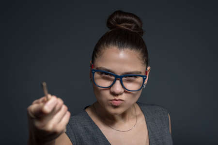 close-up portrait of a brunette girl, strict teacher in glasses, looking at the camera, pointing with a pointer to the culprit. A strict young girl of twenty-seven years old Stock Photo
