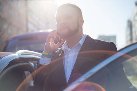 Portrait of a smiling businessman in a business suit, talking on a smartphone, getting out of the car. Outdoor. A business young man of twenty-five years old, generation Z. A bearded guy Banco de Imagens