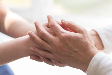 A young hand holding an elderly pair of hands hands of an old woman touch the hands of a young girl, closeup. Psychological assistance, the doctor is a therapist, a psychologist takes the patient's hand. Give hope, hands old and young, helping, helping hand.