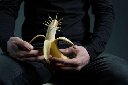 sexually transmitted diseases concept. A man in black with a prickly banana in his hand, on a gray background. Muditsin concept of sexually transmitted diseases. Sexually transmitted diseases. Diseases of the penis, glans penis, syphilis, gonorrhea, chlamydia, candidiasis of the genitals of men. Testicular disease, men's health. Imagens