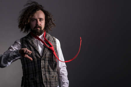 studio portrait in motion of a young bearded, curly haired guy of thirty years, in a plaid vest, and a flying red tie, waving long hair, holds his thumb down. On a gray background, a dynamic portrait. advertisement of a red mans tie. Dramatic light. Dark man portrait. curly hair. Spoiled guy. caprice. Emotional photo of a man. The thumb holds down. no, sadness, shit, it didnt work, negatively. Not suitable. damn it. bad guy. Thumb down.