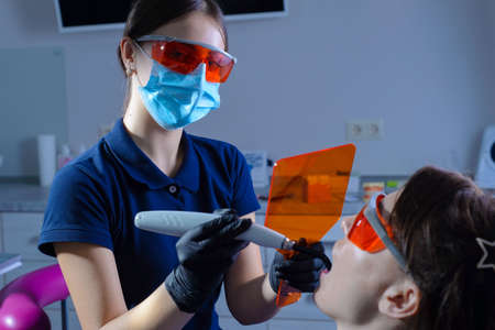 Portrait of a dentist doctor performing the procedure of professional teeth whitening using ultraviolet radiation. Patient and doctor in protective orange glasses. On a gray background. At the dental clinic. prevention and treatment of diseases of the oral cavity including teeth. Safety measures for ultraviolet procedures on the body. Aesthetic dentistry. ultraviolet filling