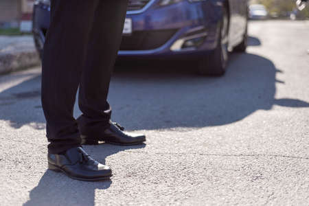 male legs in black leather shoes and black trousers, against the background of a silhouette of a car in blur. Banque d'images