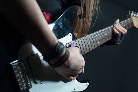 Portrait of young woman holding electric guitar in black and white close-up female hands play hard rock and roll rhythmic figure. Studio photo on a gray background