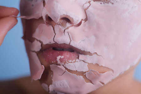 The face of the woman with a cosmetic mask. The concept of spa, beauty and skin care. Girl with pink flowers. Banque d'images