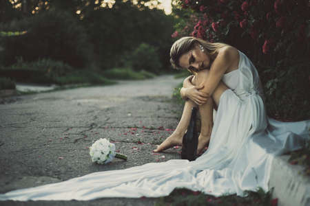 Lonely bride thrown on the wedding day, drinking alcohol from a bottle, sitting on the pavement in a white dress. against the background of red rose flowers. In a warm artistic tint. The bridegroom threw the bride on their wedding day. Runaway sad bride lonely.