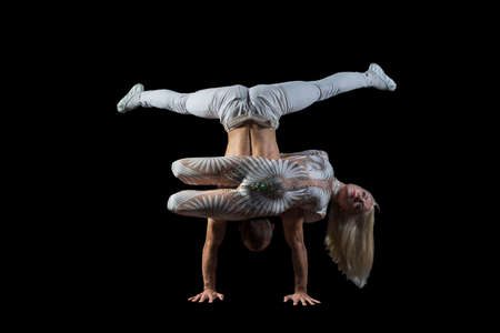 Man and woman with acrobatics pose portrait of acrobats guy with a girl in white isolated on a black background. Acrobatic abilities, sport dancing, active lifestyle, perform acrobats stunt on the floor.