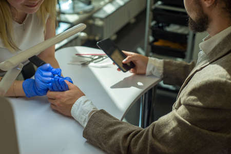a business man in a suit of thirty years old using a smartphone, manicures a master girl in a nail salon. Business man makes manicure a girl master. Beauty and health of nails
