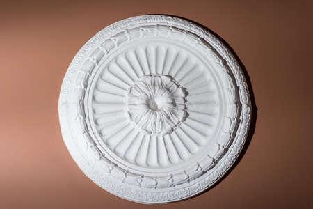 architectural decorative finish on a brown wall, white, round gypsum decorative concrete shield, texture, wall, architectural abstract concrete round. Stockfoto