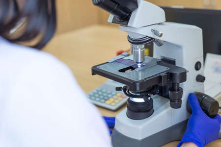 Scientist conducting research taking notes whilst looking through microscope selective focus laboratory assistant is looking through a microscope. Close-up doctor laboratory assistant looking through a microscope, determining a blood test of a patient, red blood cells, histocytologist, pathologist, examination of human tissues under a microscope. The work of a Laboratory Assistant, the workplace of a medical laboratory assistant. Stockfoto