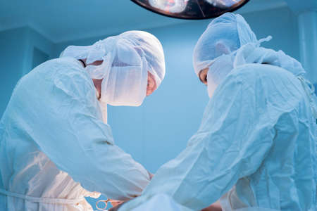 surgeon with an assistant during surgery. View from below. Children's surgery. Sterile operating room. Two masked surgeons in front of a lamp