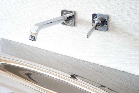 Bathroom interior with white sink and faucet faucet mixer built into the wall Stainless steel washbasin brilliant close-up. Bathroom washbasin