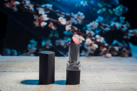 Promotional photo of lipstick, against the background of spring white flowers of cherry. Brown lipstick