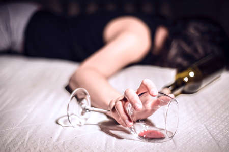 a young girl suffering from chronic alcoholism lies in a dirty room, next to a bottle of wine and a glass. Death from alcohol overdose. Problems of female excessive drinking. Depression, death