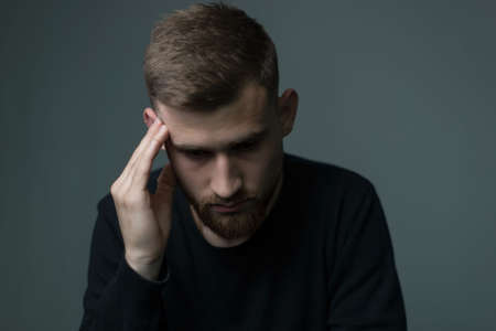 suffering from headache a young bearded guy of about twenty five, in black, presses his hand to his head, suffers from a headache. On a gray background. Depressed state, unhealthy guy, headache, migraine, mental health, upset, weakness, dizziness Фото со стока