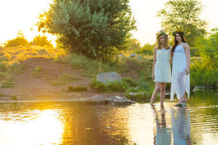 two girlfriends, young girls in white dresses and flower wreaths on their heads, standing in a river of water, near the shore, laughing, against the setting sun. The concept of virginity