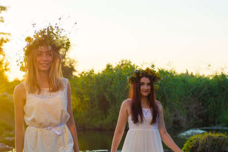 two girlfriends, young girls in white dresses and flower wreaths on their heads, standing in a river of water, near the shore, laughing, against the setting sun. The concept of virginity Stockfoto