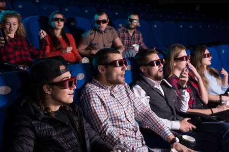 The general plan of young people of different sexes from nineteen to thirty years. Exciting emotions from the audience of the cinema. when watching a movie. Surprise.