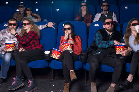 Loving couples hugging while watching a movie, and only a lonely girl sadly takes possession of the sweets of celibate loneliness. a group of young people of different sexes sitting on chairs Stockfoto