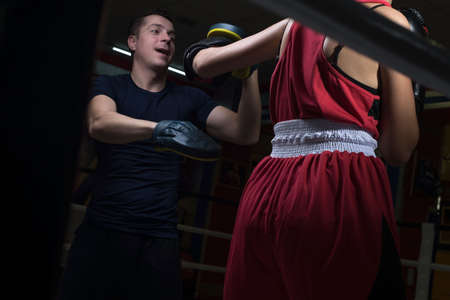 Portrait of a boxing trainer guy training a young athlete training her in martial arts. In a boxing club. Girls learn self-defense, martial art.