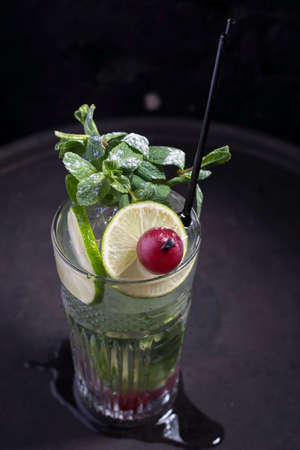close-up, advertising shot of a light alcoholic cocktail, with a sprig of mint, icing sugar, with decorative grape berry. In a rustic style, on a dark background. Stockfoto