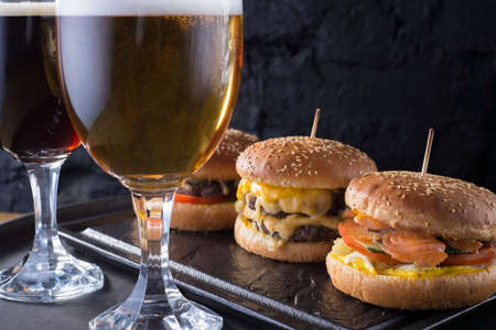 close-up, beer glasses with craft dark and light beer with foam, against a background of burgers, with a variety of ingredients, including shyomga, beef meat patty, cheese burger. In a rustic style