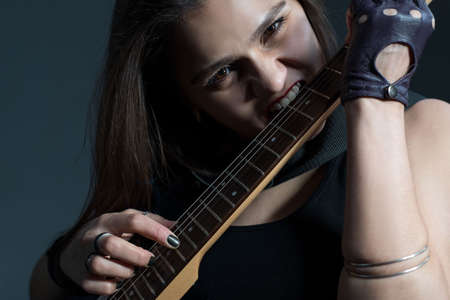 beautiful girl nibbles electric guitar fretboard. Close-up studio photo on a gray background. Stockfoto