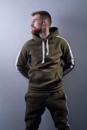 Studio portrait of a young bearded guy of twenty-five years old. in a sports jacket with a swamp-colored hood. On a gray background. green military color. In wireless headphones Stockfoto