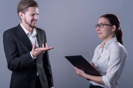 portrait of young business people in business clothes. The guy is outraged about the report of a business girl with a folder for documents. Studio photo on a gray background.