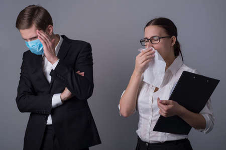 Portrait of two young businessmen in business clothes. The masked guy covers his face with his hand, fearing infection by a sick girl. which sneezes into a handkerchief. Stockfoto