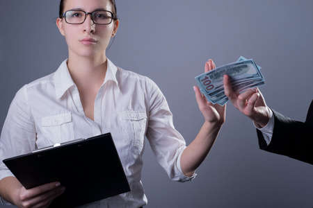 Portrait of a business girl in glasses with serious emotions on her face, with a hand prohibits giving her dollar bills from a man, against the backdrop of a bribe. Studio photo on a gray background