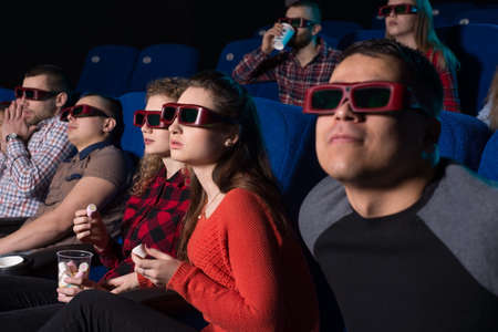 young people of different sexes from nineteen to thirty years. A variety of emotions of people in the cinema, when watching a movie, with the premise of a different perception after watching a movie. Stockfoto