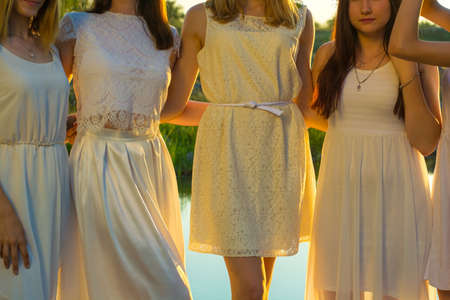 a group of young girls of twenty years old, in white dresses, with wreaths of flowers, hugging, standing against the sunset at the pond.