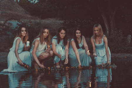a group of young tangled girls in white dresses, launching flower wreaths in the water hold candles. On a natural background. A rustic style, a national holiday for young brides