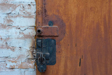 garage door lock with rusty door Combination of screw and padlock Old Orange Padlock on Wooden Blue Gate, Close up Image