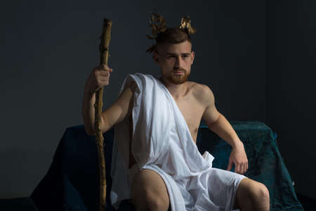 Portrait of the ancient Greek god Olympus, in white clothes, with a wreath on his head, holds a staff, sitting on a dark bench. On a gray background.