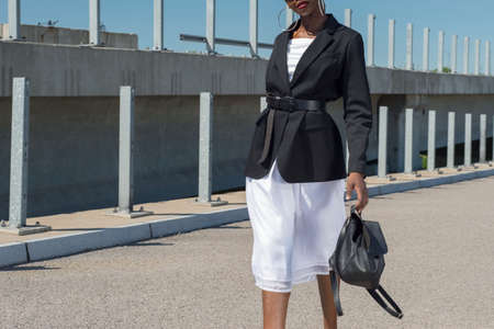 Fashionable African girl in a business jacket and white dress holds a backpack in her hand. Shooting fashion advertising against the blue sky