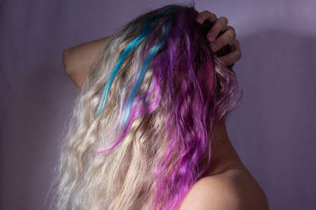 portrait of a girl covering her head with multi colored hair. On a pink background. Beauty girl, coloring in pink hair, purple shade of female hair. Turquoise hair color of a young girl Closeup of an alternative girl with multi-colored hair looking up