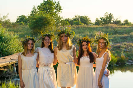 a group of young girls of twenty years old, in white dresses, with wreaths of flowers, hugging, standing against the sunset at the pond. National holiday of brides