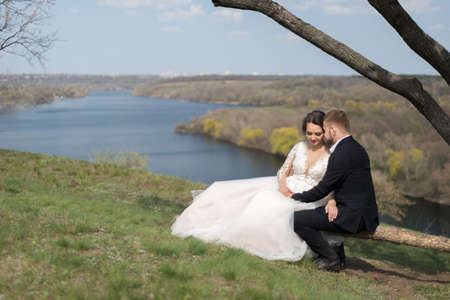 Young wedding couple of the groom with the bride kissing, cuddling, on a natural background. Summer wedding.
