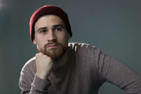 Portrait of a young bearded guy in a sweater, and a red hat, smiling. Studio photo on a gray background.