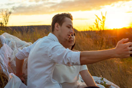 young couple of bride and groom in a grassy field, take a selfie from a smartphone. White wedding dress. The guy in the white suit. Loving couple taking selfie on smartphone camera while sitting in grass Composite of Couple taking selfie on smartphone