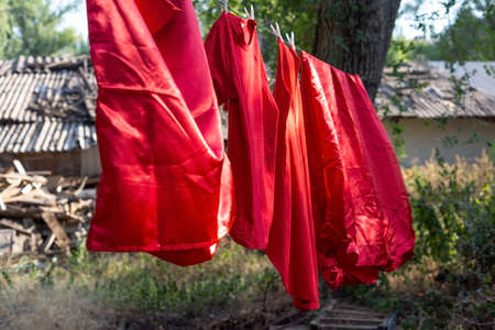 red silk bedding, sheets, rope dry, hanging outside Red woven fabric drying in the sun at Nampan Village on Inle Lake. Cloth made from lotus fiber is woven and died before making into robes for the