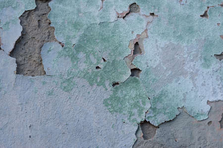 green cracked texture of plaster, with elements of rubbed gray paint. The pastel tone of a textured street wall. Crack in the wall, multiple holes in the old green plaster Green plastered brick wall texture. Gray painted retro wall built structure. Grungy shabby uneven painted plaster. Cracked biscay green plaster. Trendy background for your projects.