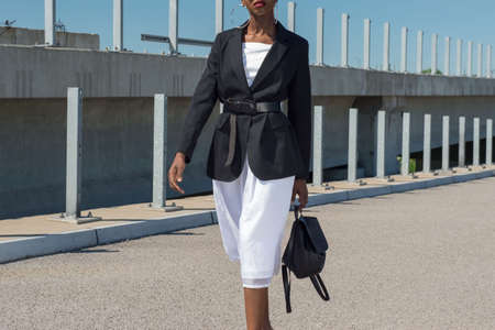 Fashionable African girl in a business jacket, and a white dress, holds a backpack in his hand. Fashionable advertising shoot against a blue sky. A young black African girl, in a black business formal jacket, over a white dress. A new fashion for wearing a belt at the waist over a female business black jacket. Relkma of a female leather backpack close-up. Beautiful black girl with a white dress posing