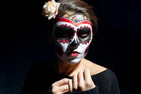 portrait of a Mexican girl in Halloween makeup. On a dark background. Sugar skull girl in hat, studio shot Imagens