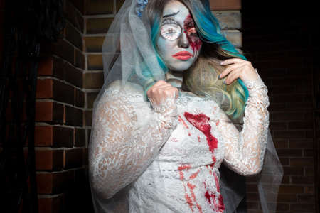 Halloween concept of bride in white dress and bloody makeup, mystical devil bride Battered woman with blood, violence and horror