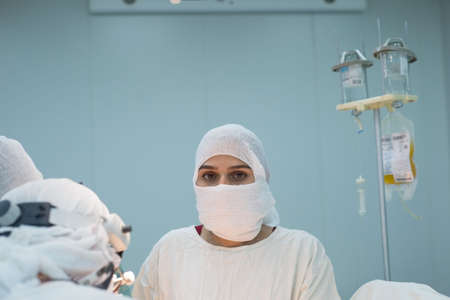 operational team. Girl surgeon looking at the camera during an operation. Conditions for a sterile operating room. Surgical intervention on the internal organs of the patient